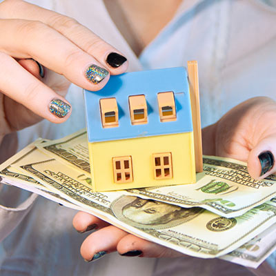 A woman holds a model house and money.