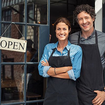 A couple stand in front of a small business.