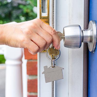 A person placing a key into a door.